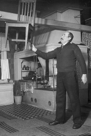 En man lyfter en stol med sin ena hand. Bilden är tagen 1938 i Närpes, Näsby.