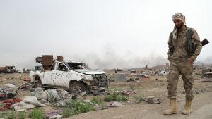 Kurdisk soldat vandrar förbi förstörd materiel i västra Syrien som använts av islamiska staten IS.