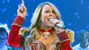 Mariah Carey sjunger i julinspirerad kraftigt urringad dräkt.