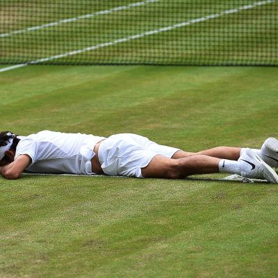 Roger Federer ligger utmattad på planen i Wimbledon-semifinalen mot Milos Raonic.