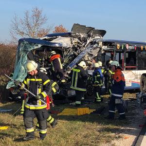 Två skolbussar som har krockat med varandra, räddningspersonal går omkring runt bussarna.