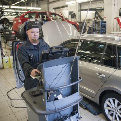 Asentaja Timo Niskanen tekee ohjelmistopäivitystä autoon.