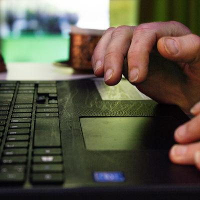 Tanjan kädet ja tietokone. Taustalla näkyy Tanjan kotia.