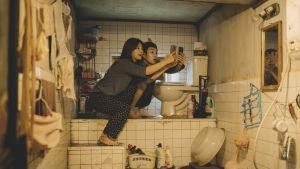 Kim Ki-jung  (So-dam Park) med brodern Woo-sik Choi (Kim Ki-woo) sitter vid toaletten och försöker få wifi till sina mobiler.