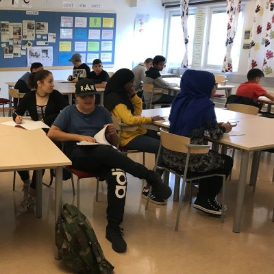 Högstadieelever sitter runt bord i ett klassrum med papper och penna framför sig.