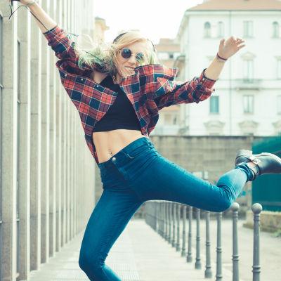 En kvinna som lyssnar på musik i hörlurar. Hon står på en gata och hoppar högt i luften. Ser glad ut.