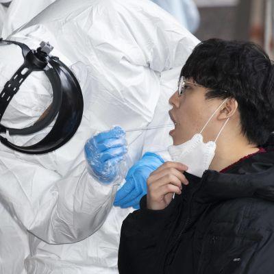 Hälsovårdsarbetare i skyddsutrustning tar covid-19-prov ur munnen på en person. Fotograferat i Seoul i mars 2020.