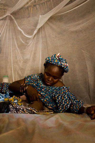 En kvinna ammar sitt barn under ett myggnät i Afrika. De ligger på golvet.