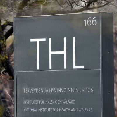 """Skylt där det står """"THL Institutet för hälsa och välfärd."""" I bakgrunden träd som börjat blomma."""