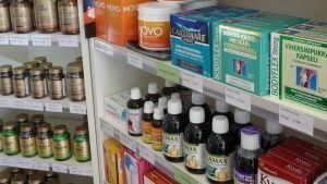 hylla med pillerburkar och förpackningar med kosttillskott.