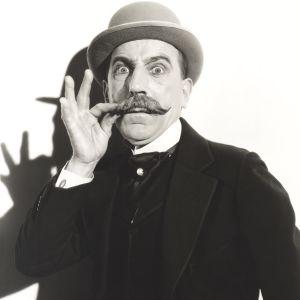 En man med en stor mustasch och en fin hatt.