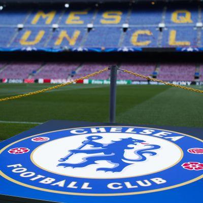 Chelsea FC:s logo med läktare i bakgrunden.