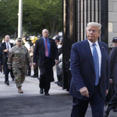 Donald Trump kävelee. Hänen taustallaan näkyy kenraali Mark A. Milley.