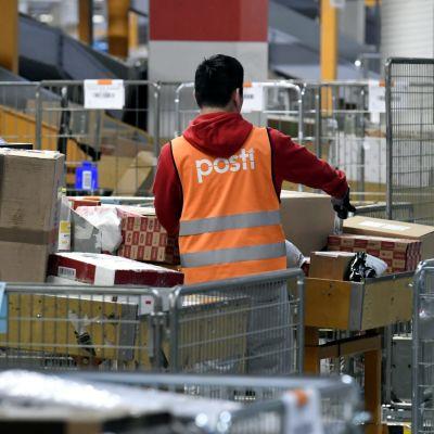 En man i orange posten-väst sorterar paket.