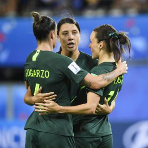 Tre australienska fotbollsspelare står i en ring.