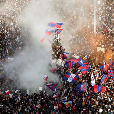 Valtava ihmisjoukko heiluttaa lippuja.