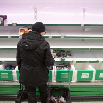 En person står framför en nästan tom butikshylla.