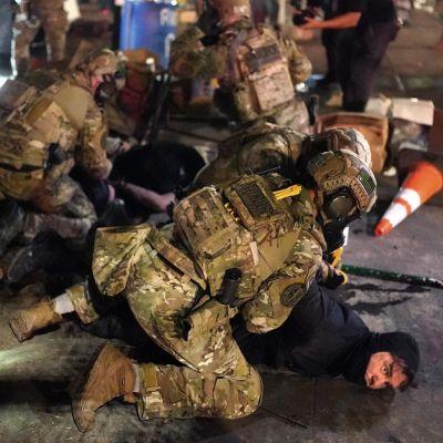 Sotilasasuun pukeutunut liittovaltion virkailija painaa maahan mustiin pukeutunutta mielenosoittajaa, taustalla lisää joukkoja sekä pehmolelunalle