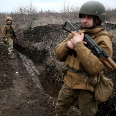 Två ukrainska soldater patrullerar längs en lerig löpgrav