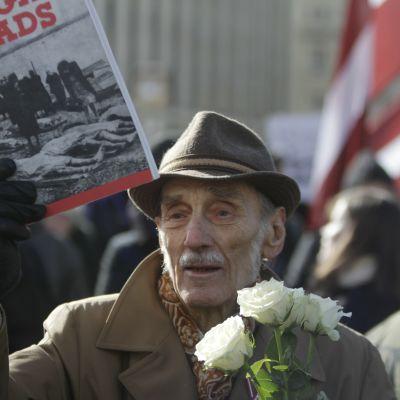 En legionärveteran håller upp en bok om den sovjetiska terrorn under minnesmarschen i Riga