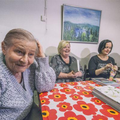 Naiset istuvat pöydän ääressä.