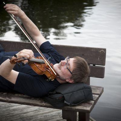 Mies makaa selällään penkillä järven rannassa ja soittee viulua sylissään.