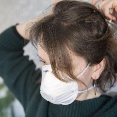 nainen asettaa itselleen maskia