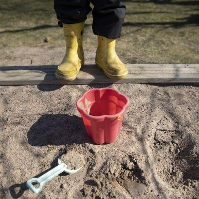 lapsi seisoo hiekkalaatikon reunalla
