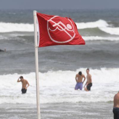 I förgrunden en röd flagga som signalerar att man inte ska simma, i bakgrunden en strand och folk som simmar i vattnet.