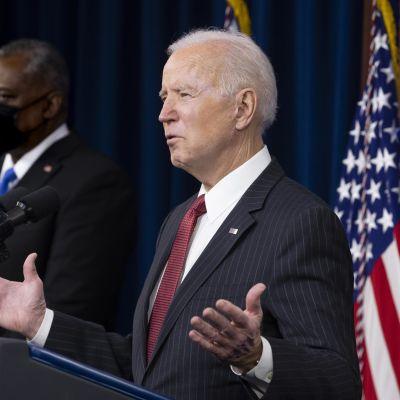 USA:s president Joe Biden håller tal och gestikulerar mer armarna. I bakgrunden står USA:s försvarsminister  Lloyd Austin