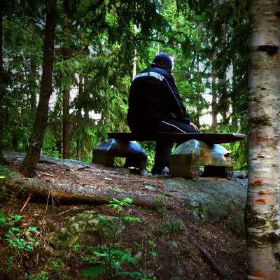 Man sitter ensam och bortvänd på bänk i skogen.