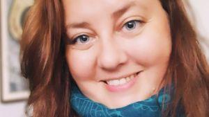 En leende kvinna med långt brunt hår.
