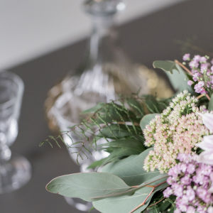 En vinkaraff av glas och en blombukett i lila.