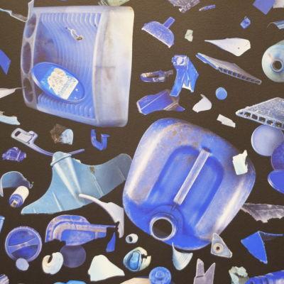 En fototavla med plastskräp i blått. Bakgrunden på tavlan är svart.