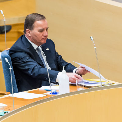 Stefan Löfven sitter på sin plats i riksdagens sal och lyssnar.