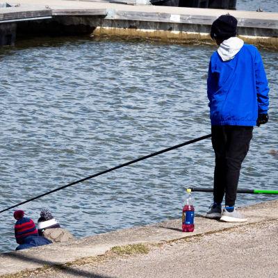 Poika kalastaa ja kaksi hänen kaveriaan istuu ja katselee.