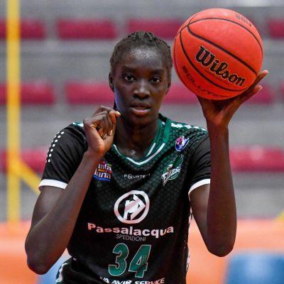 Awak Kuier i mörkgrön spelblus med basketbollen i vänster hand.