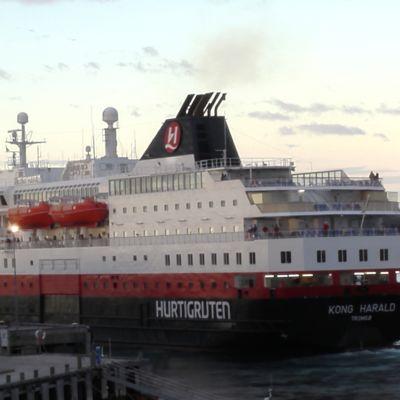 Hurtigrutens passagerarfartyg Kong Harald på väg ut ur Vardö hamn i Norge.