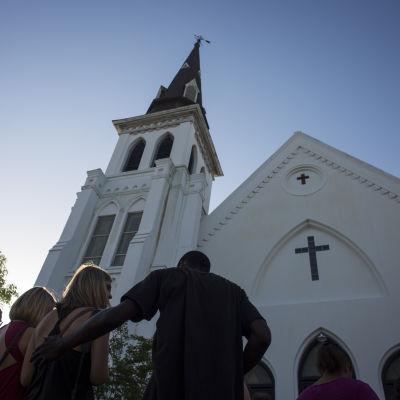 Folk tröstar varandra utanför den kyrka där skjutningen i Charleston ägde rum