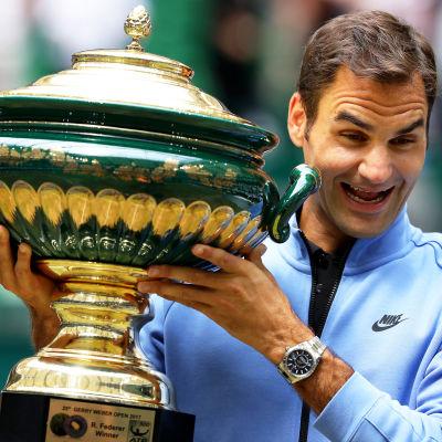 Roger Federer ser lycklig ut med en pokal i handen.