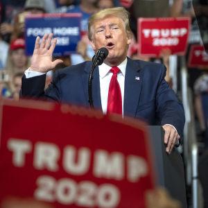Donald Trump håller upp ena handen och håller ett tal inför publik i Orlando.