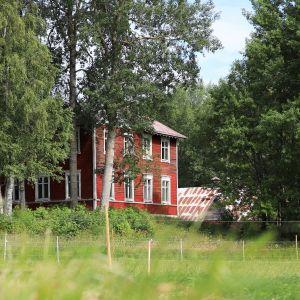 Rött hus sett från en åker.