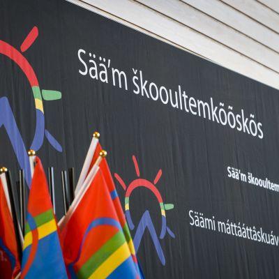 Saamelaisalueen koulutuskeskuksen logo ja saamenlippu