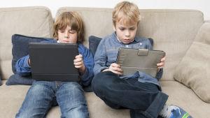 Två unga pojkar sitter i soffa och tittar på varsin pekskärm