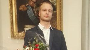 Jimmy Holmberg håller en blombukett efter att ha fått Gunnar Mickwitz pris vid Helsingfors universtet.