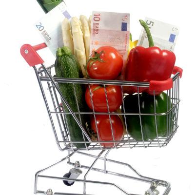 En kundvagn med grönsaker och eurosedlar i sig.