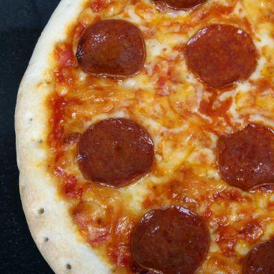 Närbild av en pizza med pepperoni.