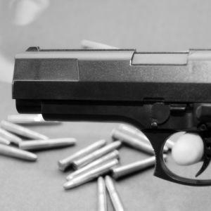 Skjutvapen med ammunition i bakgrunden.