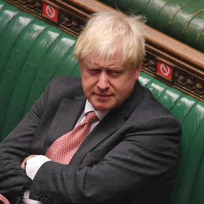 Boris Johnson sitter ensam med korslagda armar på en av de gröna bänkarna i parlamentet.