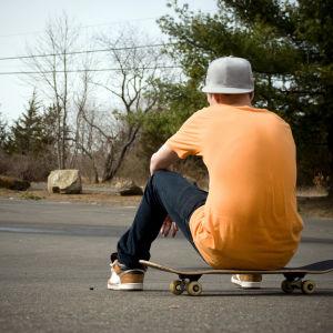 En pojke sitter på en skateboard med ryggen mot kameran.